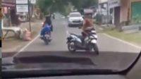 Emak-emak santuy ngobrol dengan rekannya sambil membawa motor di tengah jalan (Instagram)